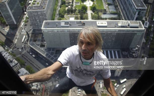 Alain Robert the French urban climber dubbed Spiderman climbs the 210m Tour Montparnasse skyscraper on April 28 2015 in Paris AFP PHOTO / KENZO...