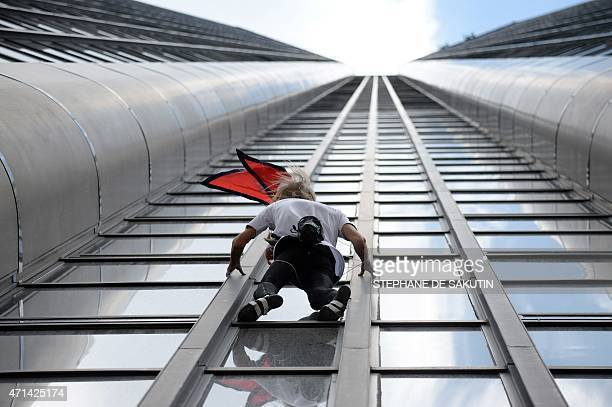 Alain Robert the French urban climber dubbed Spiderman climbs the 210m Tour Montparnasse skyscraper on April 28 2015 in Paris Robert is holding a...