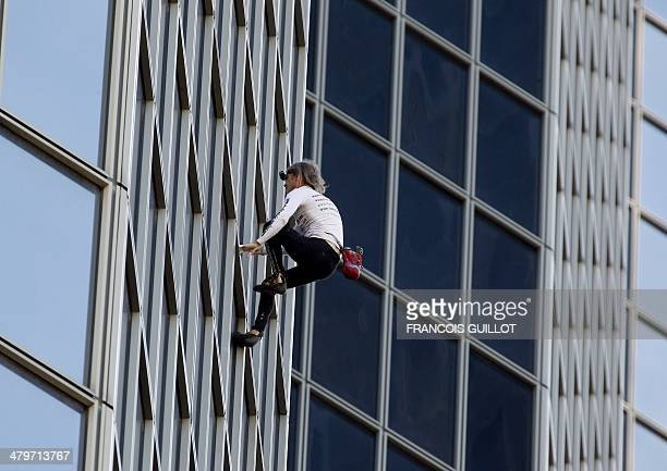 Alain Robert the French urban climber dubbed Spiderman climbs the Total company's headquarters a 186meter high skyscraper at the business district of...