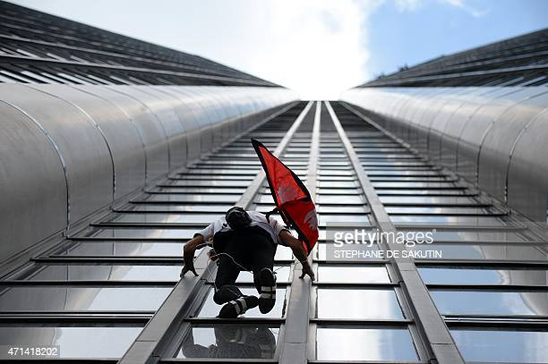 Alain Robert the French urban climber dubbed Spiderman climbs with a Nepalese flag in hand the 210m Tour Montparnasse skyscraper on April 28 2015 in...