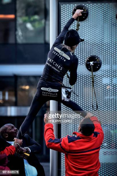 Alain Robert the French urban climber dubbed Spiderman is grabbed by security guards preventing him to climb a building hosting the headquarters of...