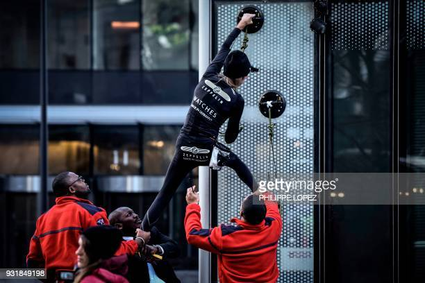 TOPSHOT Alain Robert the French urban climber dubbed Spiderman is grabbed by security guards preventing him to climb a building hosting the...