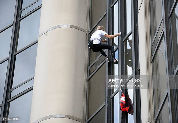 Alain Robert the French urban climber dubbed Spiderman with a Nepalese flag in hand climbs the 210m Tour Montparnasse skyscraper on April 28 2015 in...