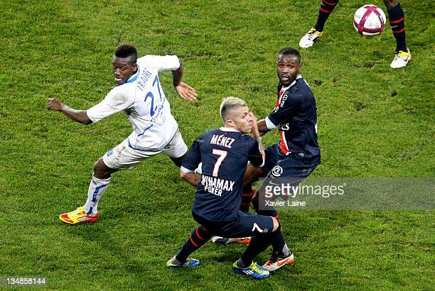 Alain Traore of Auxerre competes with Jeremy Menez and Siaka Tiene of Paris Saint Germain during the French Ligue 1 match between Paris Saint Germain...