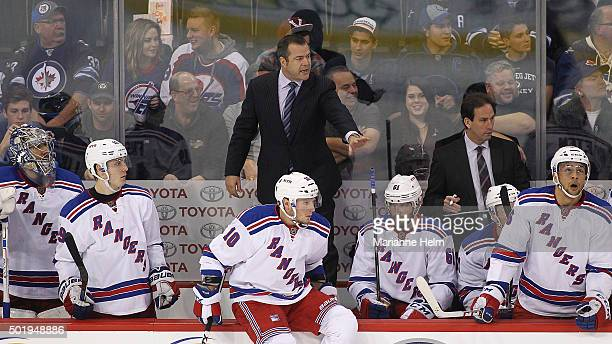 Alain Vigneault head coach of the New York Rangers stands on the bench to give directions in third period action in an NHL game against the Winnipeg...