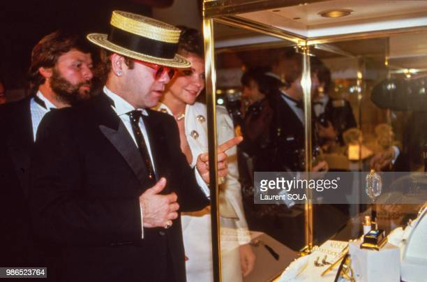 AlainDominique Perrin fait visiter l'exposition Cartier à Elton John et sa femme le 3 janvier 1985 à Gstaad en Suisse