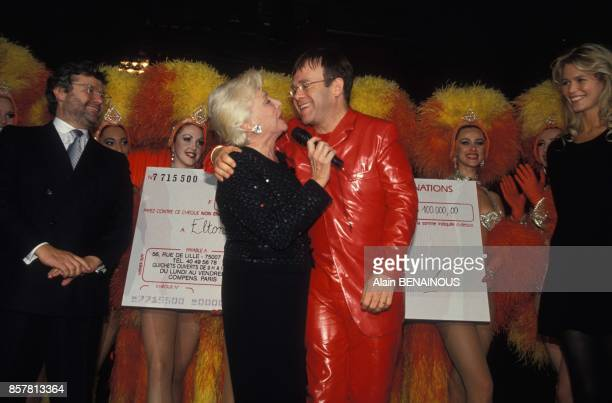 AlainDominique Perrin Line Renaud Elton John and Claudia Schiffer at party against AIDS at the Moulin Rouge cabaret on October 11 1994 in Paris France
