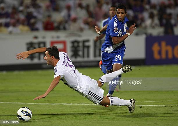AlAin's Alex Brosque stumbles against AlHilal 's Salem during their AFC Champions League group D football match at the Sheikh Tahnoun Bin Mohammed...