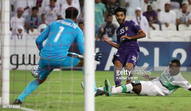 AlAin's captain Emirati forward Yousef Ahmed attempts a shot as he is marked by AlAhli's Saudi defender Motaz Hawsawi during their AFC Champions...
