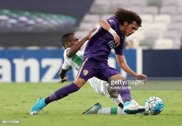 AlAin's captain Emirati midfielder Omar Abdulrahman is tackled by AlAhli's Saudi defender Motaz Hawsawi during their AFC Champions League Group C...