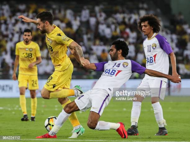 AlAin's Egyptian midfielder Hussein El Shahat vies for the ball against AlWasl's Australian midfielder Anthony Caceres during the United Arab...
