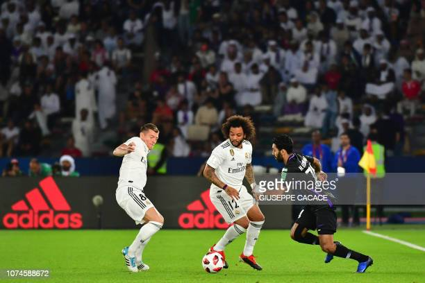 AlAin's midfielder Hussein elShahat fights for the ball with Real Madrid's Brazilian defender Marcelo and Real Madrid's German midfielder Toni Kroos...