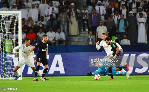 AlAin's midfielder Hussein elShahat is marked by Real Madrid's Belgian goalkeeper Thibaut Courtois during the Final match in the FIFA Club World Cup...