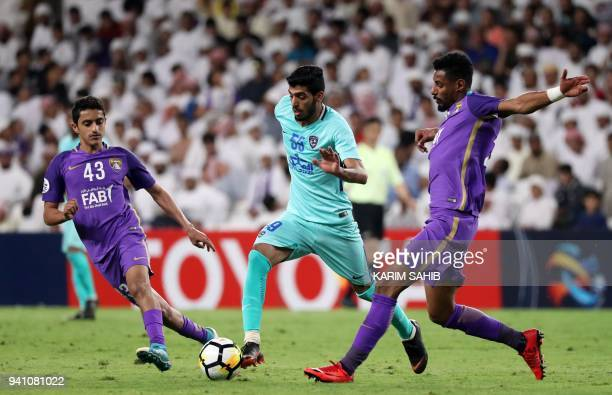 AlAin's midfielder Rayan Yaslam and defender Mohamed Ahmed vie for the ball with AlHilal's midfielder Fahad AlRashidi during the AFC Champions League...