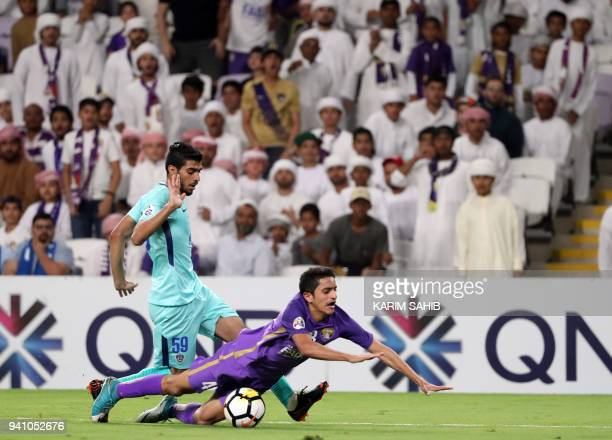 AlAin's midfielder Rayan Yaslam is fouled by alHilal's midfielder Fahad AlRashidi during the AFC Champions League football match between UAE's alAin...