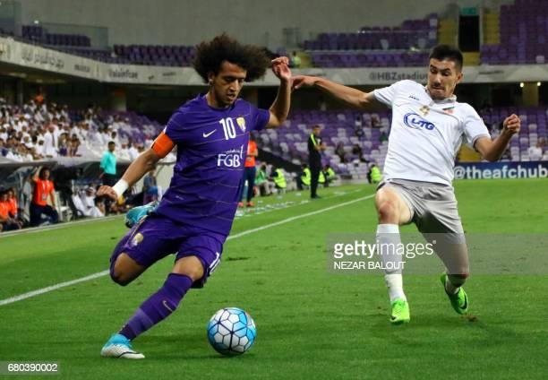 AlAin's Omar Abdulrahman and Bunyodkor's Komilov Akramjon vie for the ball during their AFC Champions League Group C football match at the Hazza Bin...