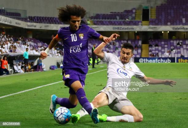 AlAin's Omar Abdulrahman is tackled by Bunyodkor's Komilov Akramjon during their AFC Champions League Group C football match at the Hazza Bin Zayed...