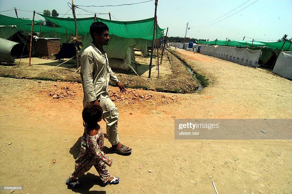 SHEICK SHAZAD CAMP, MARDAN, SARHAD PROVINCE, PAKISTAN - JUNE 29TH: Alam Zeab, the head and father of his Pashtun family is taking his youngest girl Sapna to payer, June 29th 2009, in Pakistan. He left : News Photo
