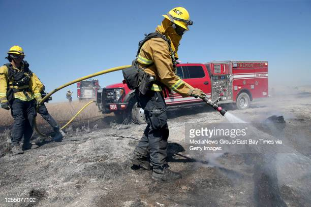 Alameda County firefighters mop up hot spots from a 40-acre grass fire in the marsh at Coyote Hills Regional Park in Fremont, Calif., on Monday, July...