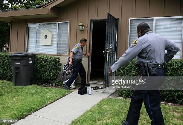 Alameda County Sheriff deputies Ken Kong and Ken Cammack move in to search a foreclosed home after a locksmith broke the lock off the door as they...