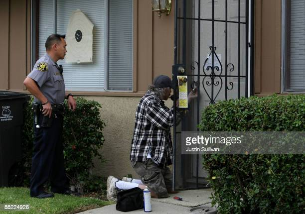 Alameda County Sheriff deputy Ken Kong looks on as a locksmith picks a lock on a door at a foreclosed home June 4 2009 in Union City California With...