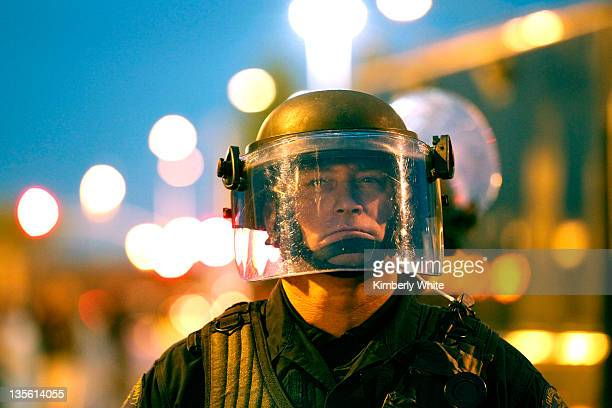 Alameda County Sheriff officer in riot gear stands watch as protesters attempt to block an entrance to the Port of Oakland on December 12 2011 in...