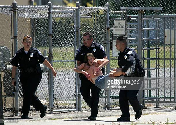Alameda Police officers carry a volunteer student with simulated injuries during a school shooting and mass evacuation drill at Lincoln Middle School...