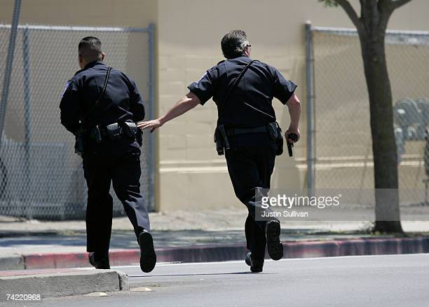 Alameda Police officers run towards a building as they respond to a school shooting and mass evacuation drill at Lincoln Middle School May 22 2007 in...