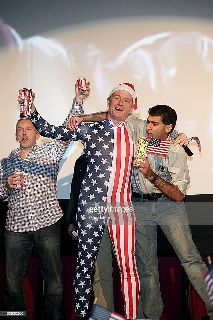 Alamo Drafthouse Co-Founder and CEO Tim League, wearing a US Flag jumper and Santa hat, leads movie goers on a sing along of 'Proud To Be An American' before a screening of Sony Pictures' 'The Interview' which opens on Christmas Day, December 25, 2014 in Austin, Texas. Sony hackers have been releasing stolen information and threatened attacks on theaters which screened the film.