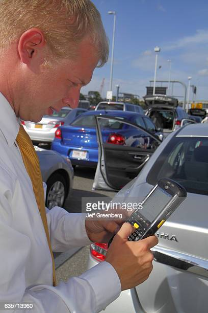 Alamy Car Rental agent using handheld computer scanner on the return of a car