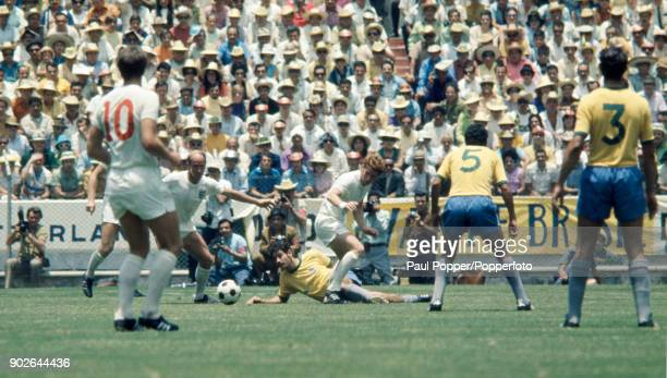 Alan Ball of England is tackled by Brazil's Roberto Rivelino watched by Bobby Charlton during the FIFA World Cup match between Brazil and England at...