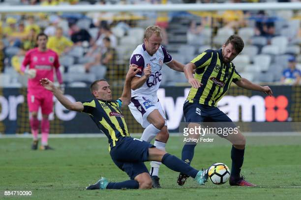 Alan Baro of the Mariners contests the ball against Mitch Nichols of Perth Glory with Antony Golec of the Mariners during the round nine ALeague...