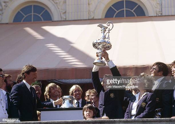 Alan Bond the Australian businessman and leader of the syndicate which owned the victorious Australia II holding the trophy during the presentation...