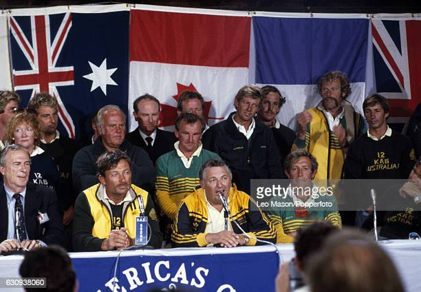Alan Bond the Australian businessman and leader of the syndicate which owned the victorious Australia II speaking at a news conference with skipper...