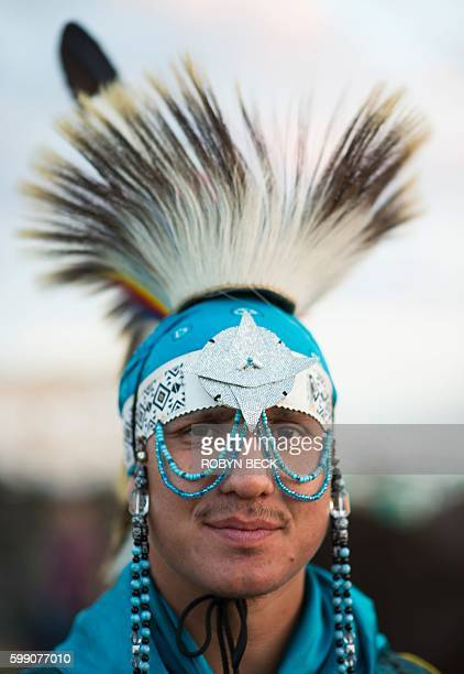 Alan Carter of the Cheyenne River Sioux Tribe is grass dancer garb poses for a photograph at an encampment where hundreds of people have gathered to...