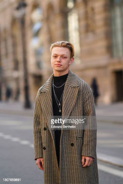 Alan Carton @alan.crtn wears a black turtleneck pullover from Zara, a necklace, a beige oversize wool long trench coat with printed houndstooth...
