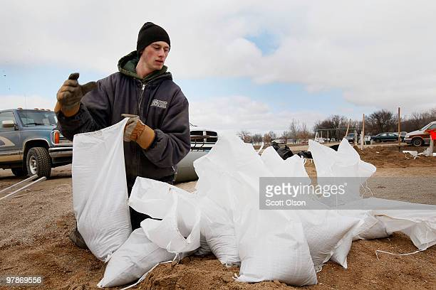 Alan Cassezza helps a friend build a sandbag levee around his home to hold back flood water from the Red River March 19 2010 near Fargo North Dakota...