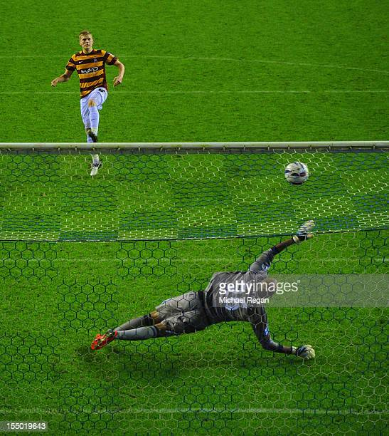 Alan Connell of Bradford scores past Ali Al Habsi of Wigan in the shootout during the Capital One Cup Fourth Round match between Wigan Athletic and...