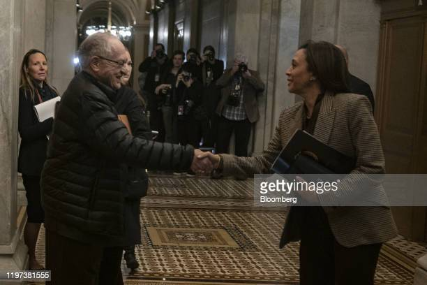 Alan Dershowitz lawyer for President Donald Trump second left shakes hands with Senator Kamala Harris a Democrat from California at the US Capitol in...