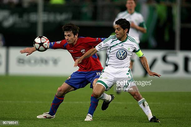 Alan Dzagoev of Moscow is challenged by Josue of Wolfsburg during the UEFA Champions League Group B match between VfL Wolfsburg and CSKA Moscow at...