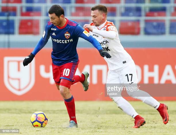 Alan Dzagoev of PFC CSKA Moscow vies for the ball with Nikolay Dimitrov of FC Ural Ekaterinburg during the Russian Premier League match between PFC...