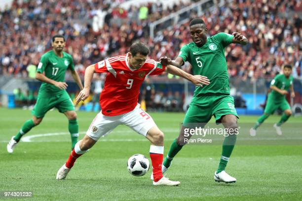 Alan Dzagoev of Russia battles for possession with Omar Othman of Saudi Arabia during the 2018 FIFA World Cup Russia Group A match between Russia and...
