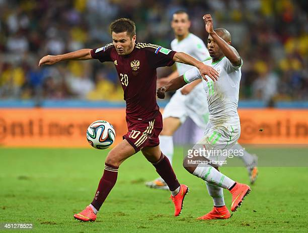 Alan Dzagoev of Russia controls the ball against Yacine Brahimi of Algeria during the 2014 FIFA World Cup Brazil Group H match between Algeria and...