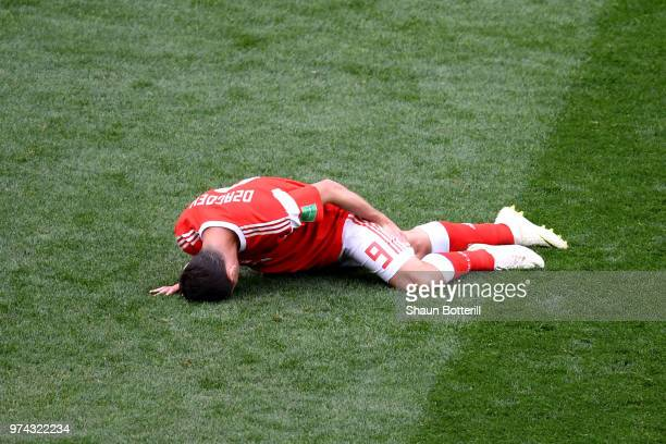 Alan Dzagoev of Russia holds his leg as he goes down injured during the 2018 FIFA World Cup Russia Group A match between Russia and Saudi Arabia at...