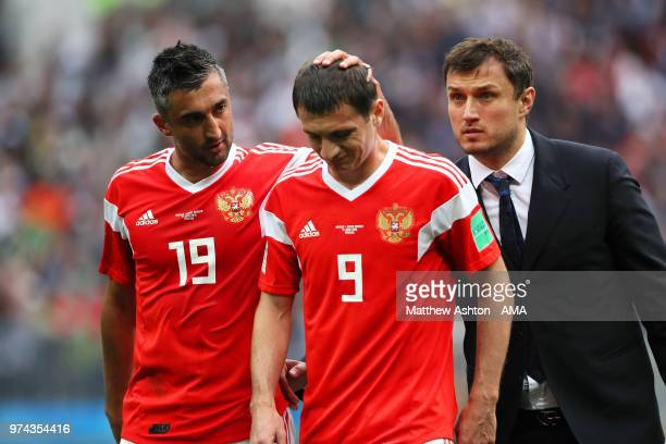 Alan Dzagoev of Russia is consoled by teammate Alexander Samedov as he goes off injured during the 2018 FIFA World Cup Russia group A match between...