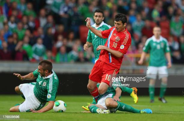 Alan Dzagoev of Russia is tackled by Craig Cathcart and Gareth McAuley of Northern Ireland during the FIFA 2014 World Cup Group F Qualifier match...
