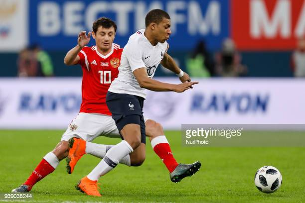 Alan Dzagoev of Russia national team and Kylian Mbappe of France national team vie for the ball during the international friendly football match...