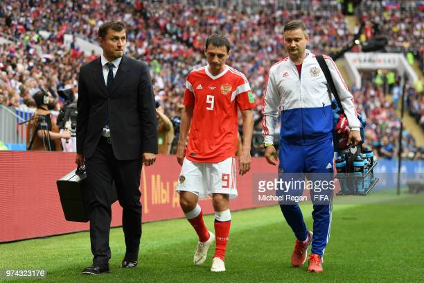 Alan Dzagoev of Russia walks off with medical staff after recieving treatment during the 2018 FIFA World Cup Russia Group A match between Russia and...