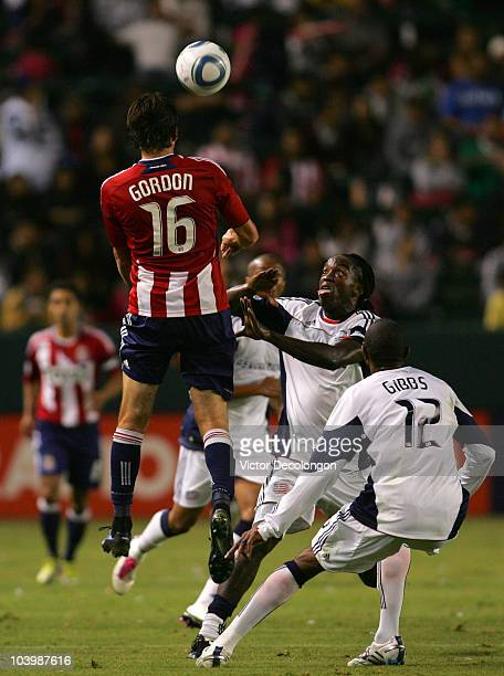 Alan Gordon of Chivas USA heads the ball as Shalrie Joseph of New England Revolution looks on in the first half during the MLS match at The Home...