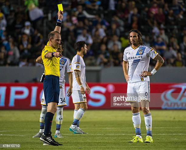 Alan Gordon of Los Angeles Galaxy receives a yellow card from Referee Ted Unkel for a foul on Liam Ridgewell of Portland Timbers during Los Angeles...